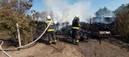 Tűzoltók oltják az égő farakást.